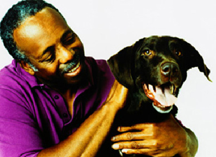man in purple shirt holding dog